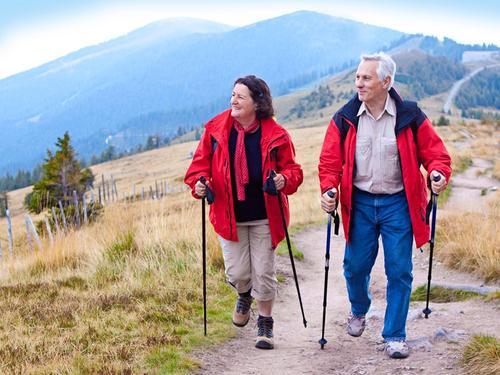 Пожилая пара ходит с палками